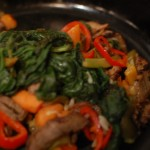 Meat, vegetables, spinach stirred in cast iron skillet.
