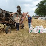 Picture of antique threshing machine, crew, pile of straw, sacks of grain
