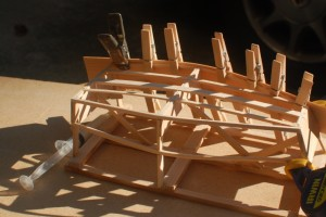 The side glued and clamped to the chine and rail on the building frame.  The clamps are small clothes pins.