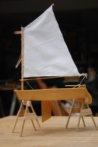 Optimist Pram model on model sawhorses.  Centerboard, rudder, and sail are in profile in this side view.