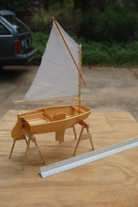 This view from slight to the rear and right side shoes the interior of the boat.  The actual boat is 7 and 1/2 feet long.  The model is about 7 1/2 inches long and 4 inches wide.  The front is square, not pointed which is the pram shape.  The hull is slightly narrower in the front, bows out amidship and tapers slightly to the transom.